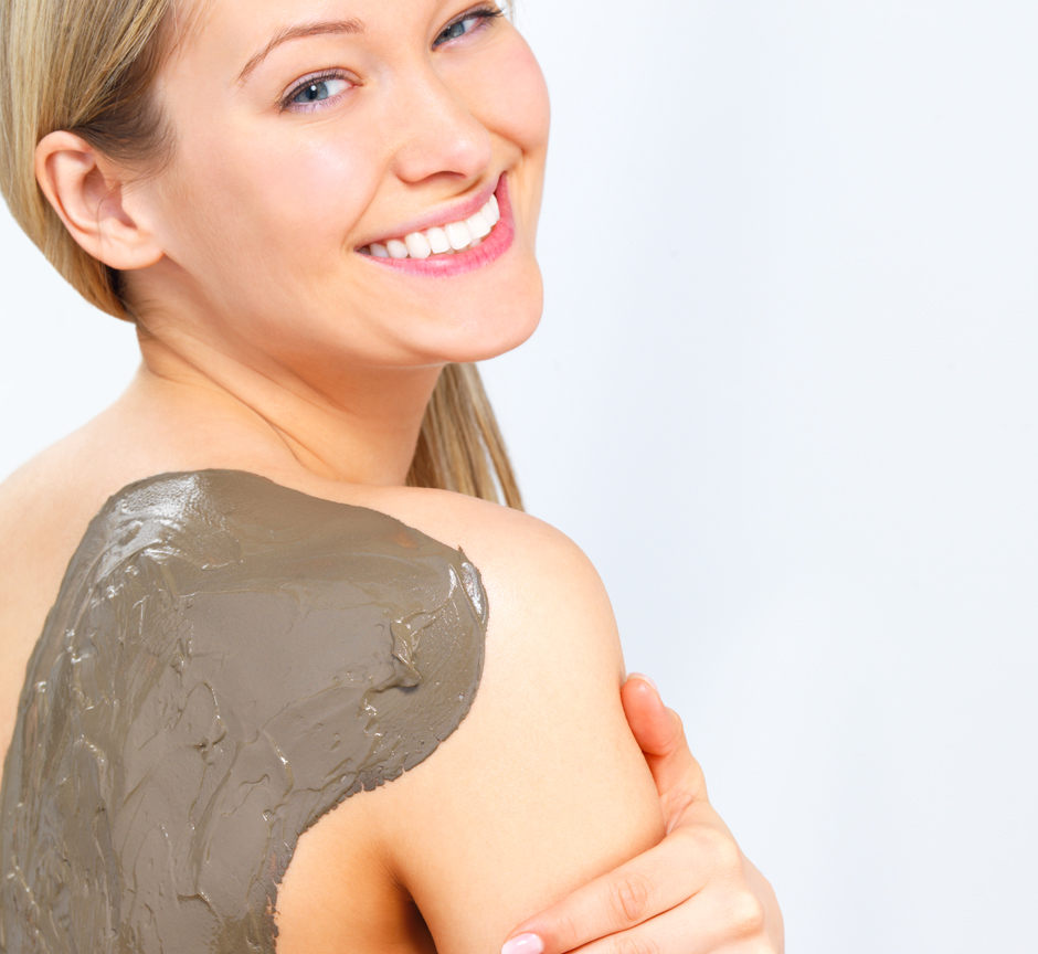 Mud treatment on the back of a young smiling female - Young woman with body mask on her back